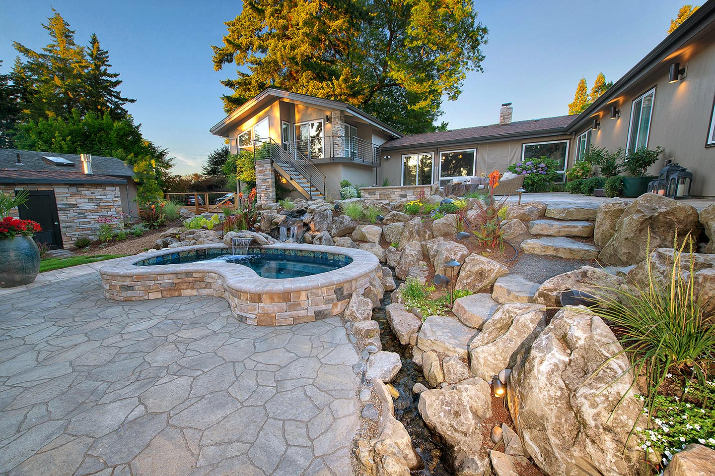 In-ground custom built spa with water feature flowing through landscape