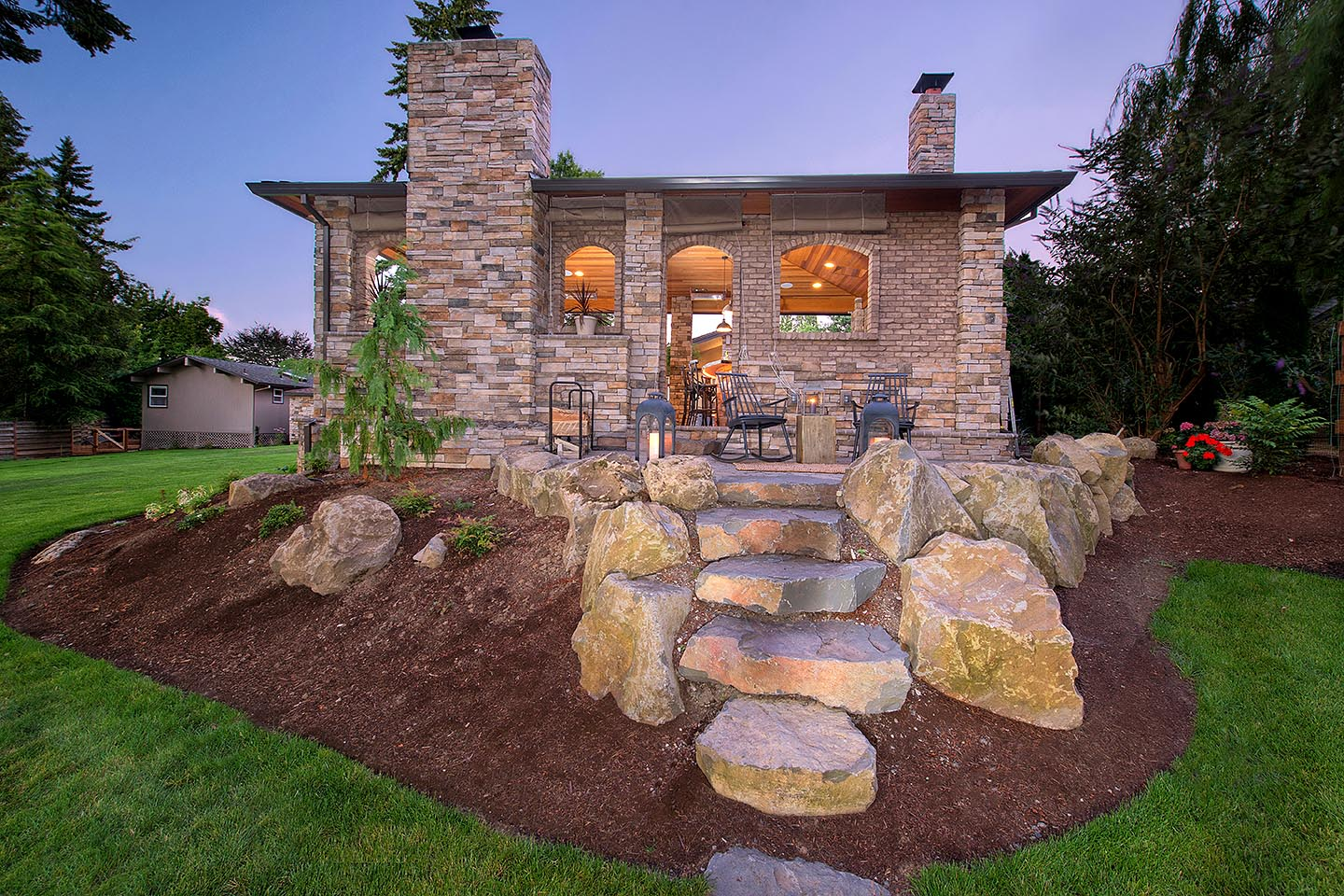 Rear view of gazebo with hardscape patio and boulder steps