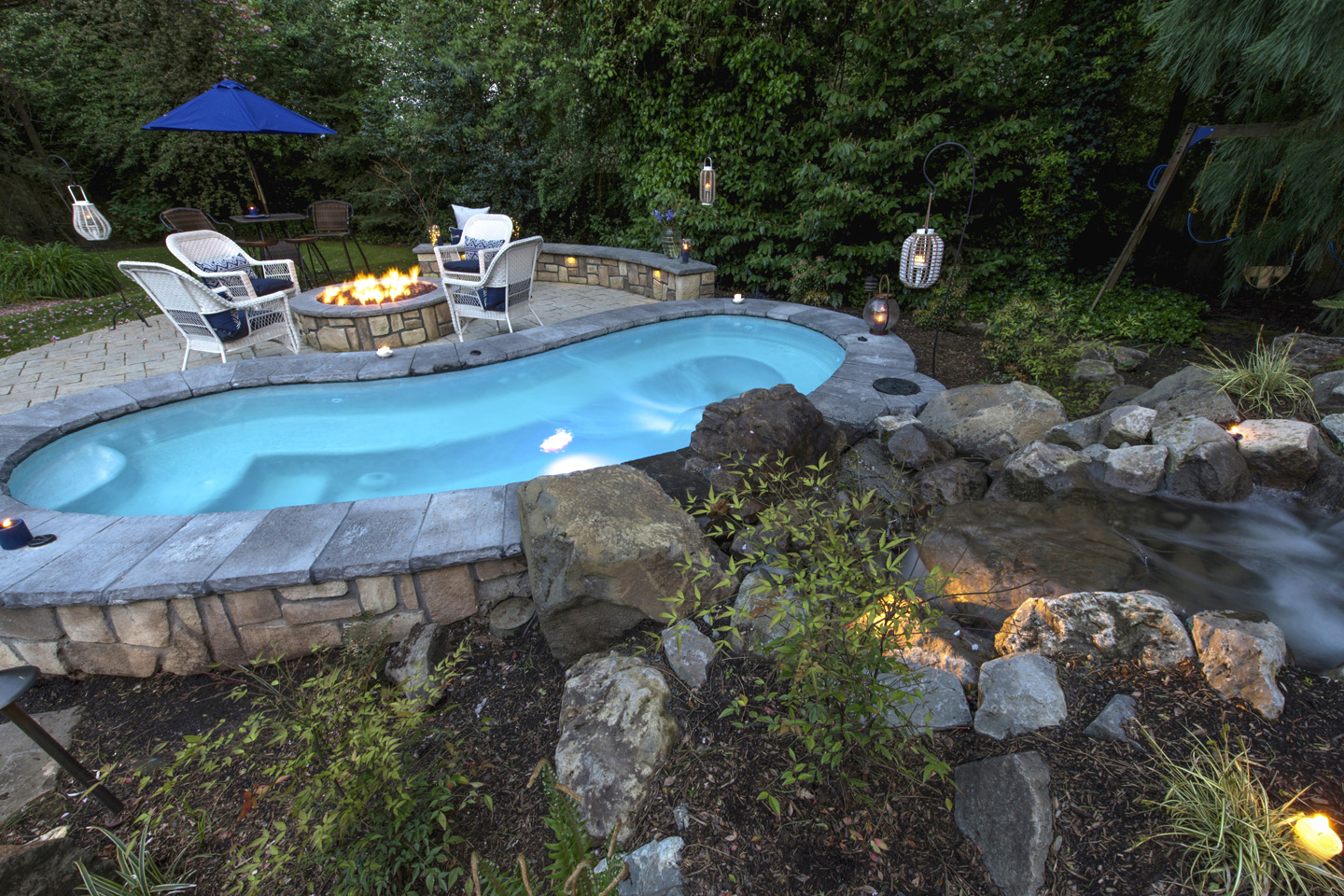 Custom in-ground spa with waterfall hardscape patio